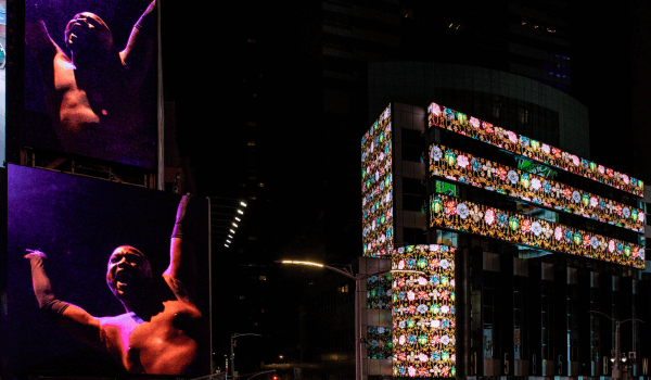 "Midnight Moment ""Black Magic"" on the Times Square screens at 47th and Broadway, showing a dancer and an animated floral pattern"