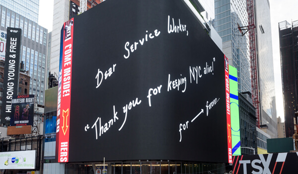 "The 20 Times Square screen with a handwritten message saying ""Dear Service Worker, 'Thank you for keeping NYC alive!' for ⟶ forever..."
