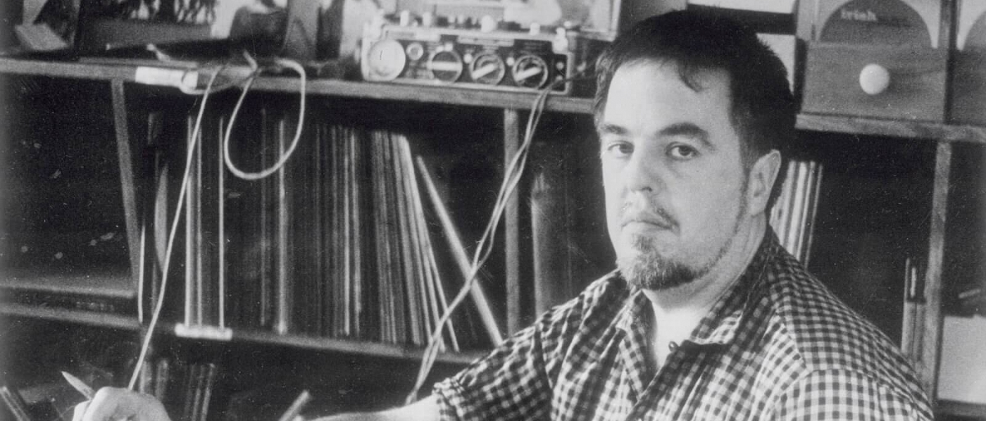 Black and white photo of Alan Lomax sitting in front of a shelf of records