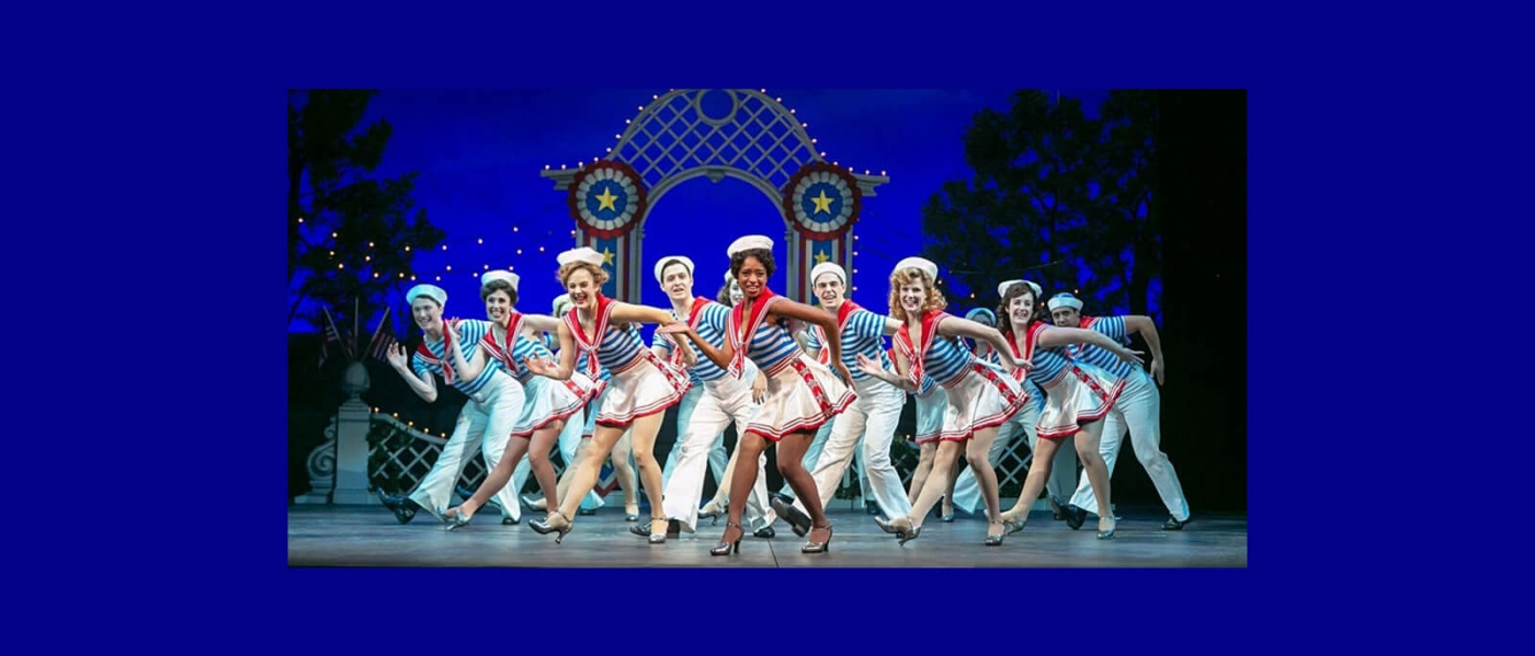 Dancers in sailor-inspired costumes on stage