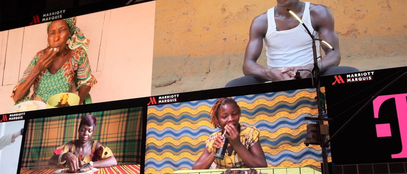 Table Manners on the Marriott Marquis screen, with four different videos showing people eating in front of colorful backdrops
