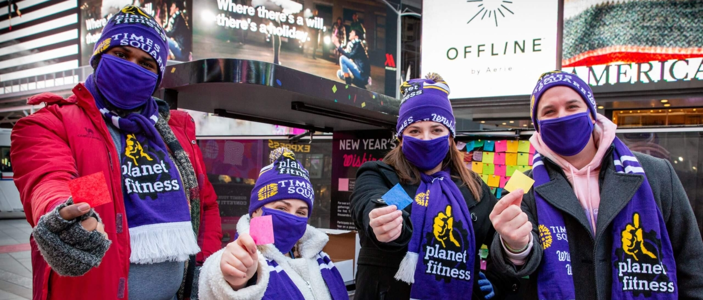 Four people in Planet Fitness hats, scarves, and masks, holding up pieces of confetti in front of the Wishing Wall