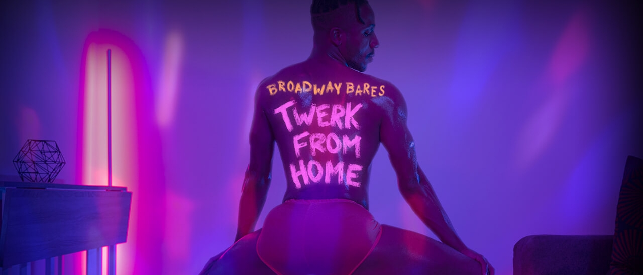 """A shirtless man in booty shorts twerks in a blacklit room with """"Broadway Bares Twerk From Home"""" written on his back in fluorescent paint"""