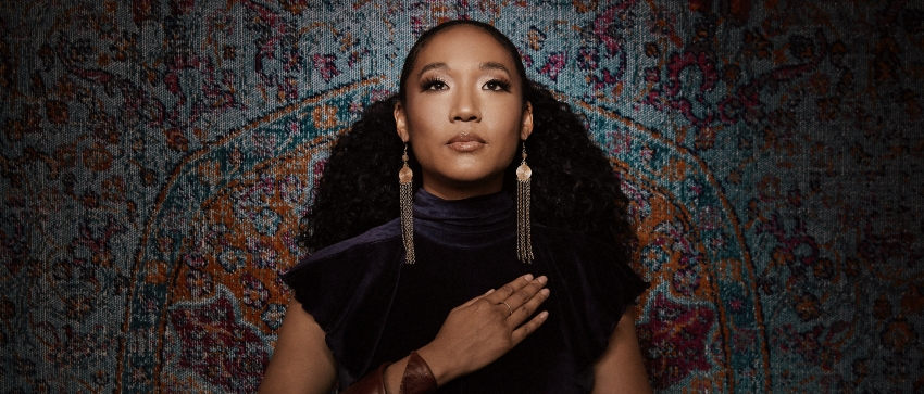 Judith Hill standing in front of a fabric background with her hand on her heart