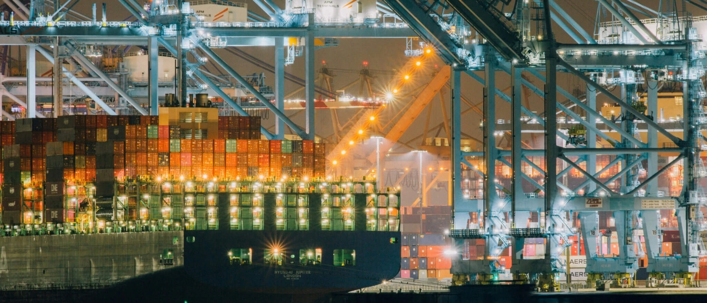 A nighttime photo of large container ships and shipping infrastructure