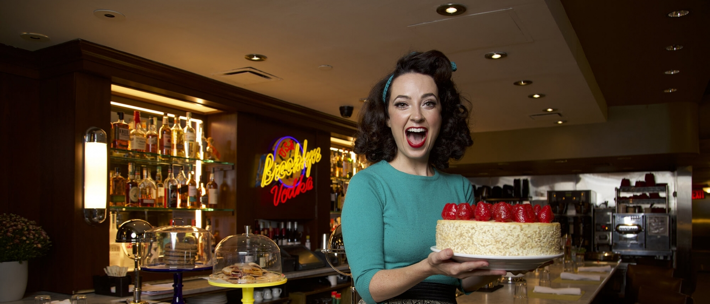 A performer sits on the counter of the Brooklyn Diner, holding a cake and looking very enthusiastic