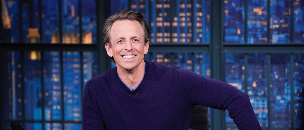 Seth Meyers behind the desk of his late-night show