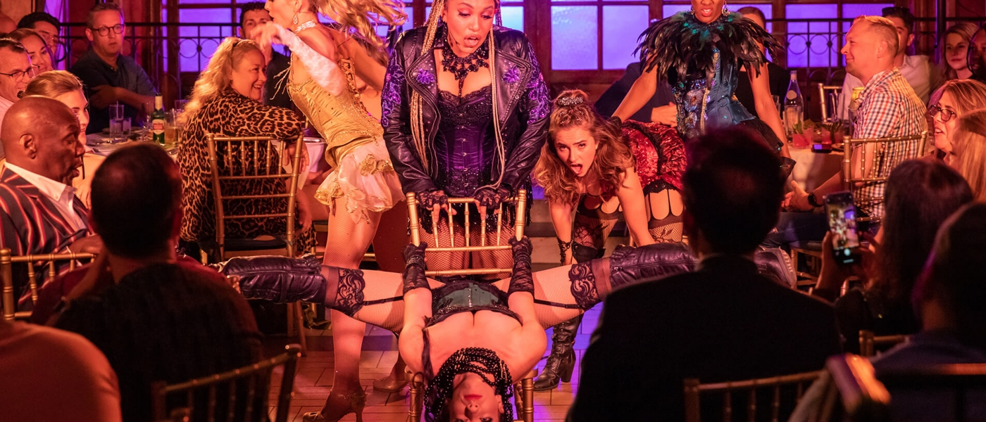 Jada Temple and company, in elaborate corsets and stockings, perform at Speakeasy; in the foreground of the image a dancer straddles a chair upside down