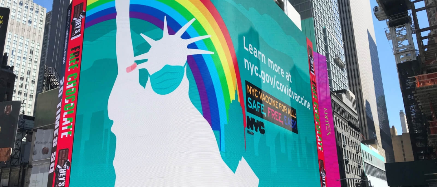 The big screen at 20 Times Square, with an illustration of the Statue of Liberty wearing a mask and information about NYC vaccinations