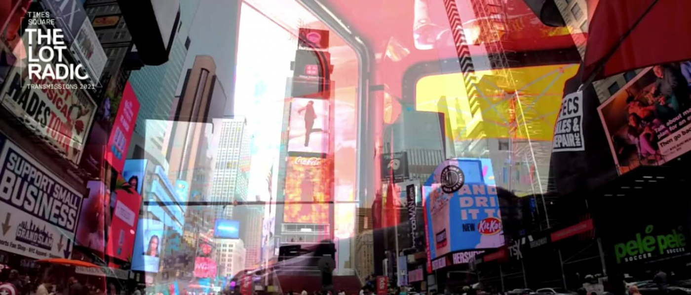 A glimpse inside the windows of the Times Square Transmissions DJ booth, with the buildings and lights of Times Square reflected onto the window