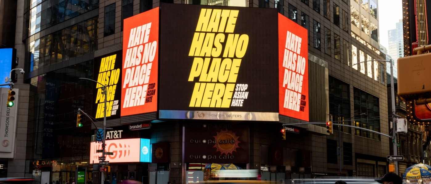 """Multiple screens at the corner of 43rd and 7th showing a work by Zipeng Zhu saying """"Hate has no place here stop Asian hate"""""""