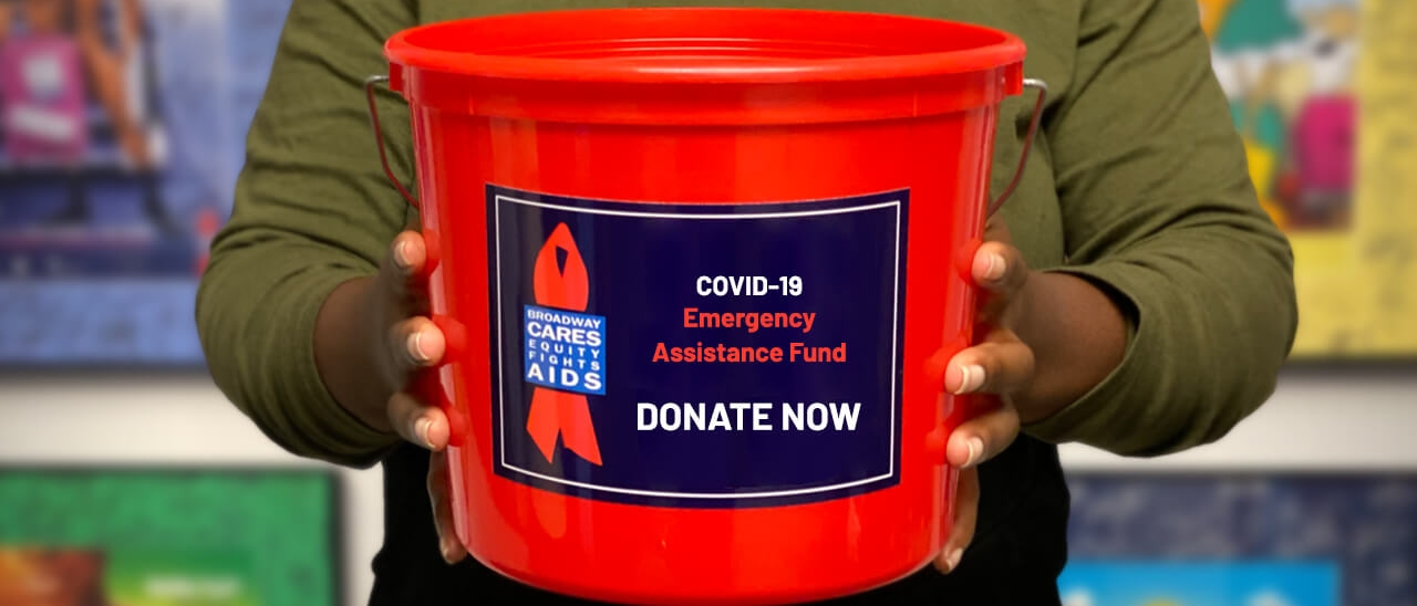 "Someone holding the iconic Broadway Cares/Equity Fights AIDS red bucket, with a label reading ""COVID-19 Emergency Assistance Fund"""