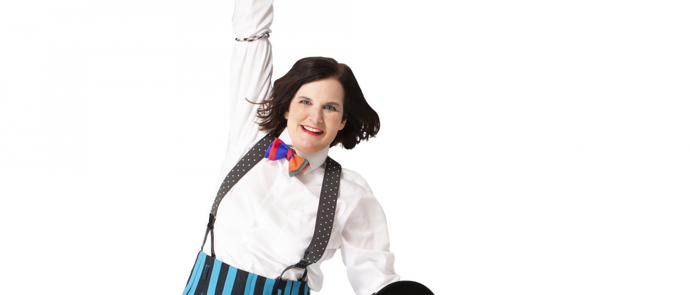 Paula Poundstone jumping while wearing suspenders and a bowtie