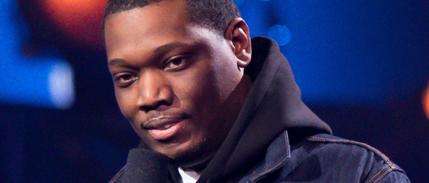 Michael Che speaking into a microphone