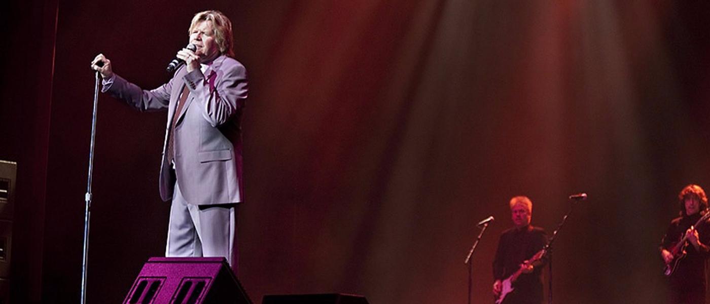 Peter Noone singing on stage