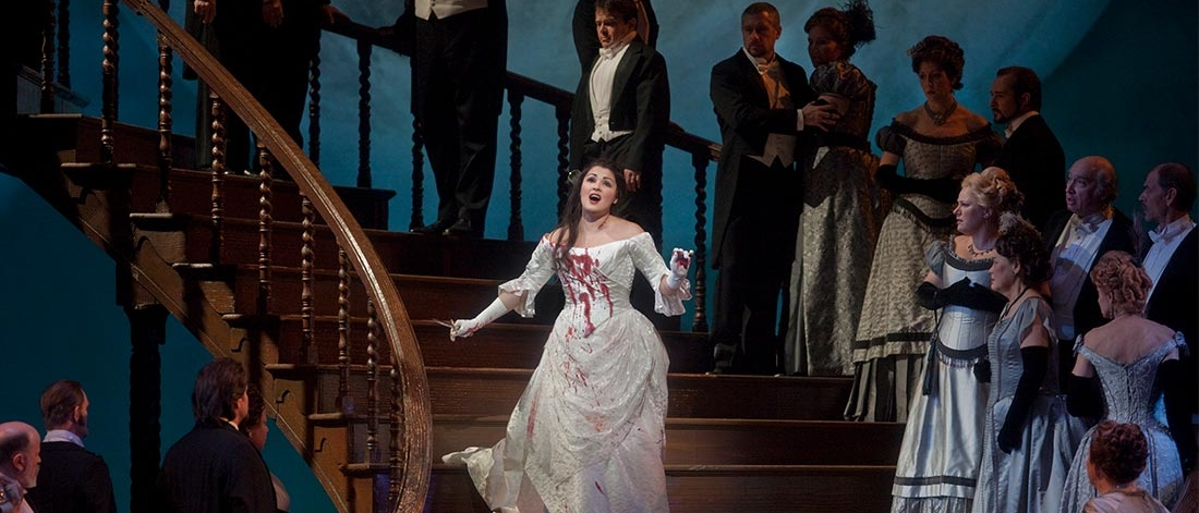 A woman singing in a bloodied gown in a performance of Lucia by the Metropolitan Opera