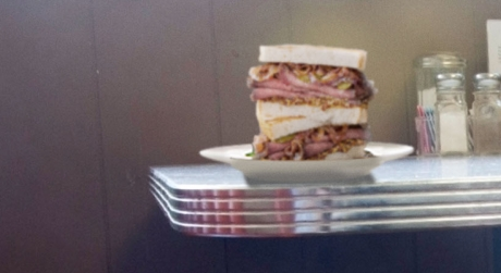 Photo of a stacked sandwich on a diner table