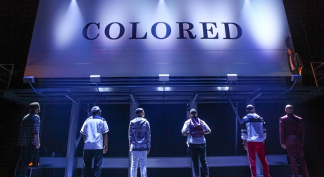 Six actors stand on a stage in dim lighting, looking up at a billboard that reads