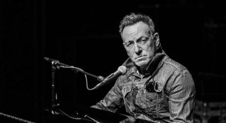 Black and white photo of Bruce Springsteen at a piano